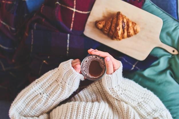 毛布で覆われた暖かいセーターを着た居心地の良い女性は、ホットココアのガラスのカップを保持しています。木の板に焼きたてのクロワッサン。上面図