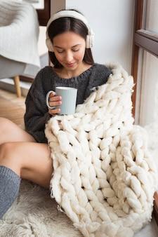 Donna accogliente con coperta e tazza
