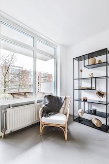 현대적인 미니멀리즘 스타일로 장식 된 우아한 라운지 구역이있는 밝고 넓은 아파트의 넓은 창 근처에 아늑한 목재 안락 의자가 배치되었습니다.
