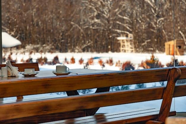 居心地の良い木製のベンチとカフェのテーブル。大きな窓を見下ろすコーヒーと、晴れた凍るような日のぼやけた冬の風景。日光のコンセプトカフェ