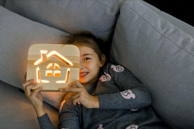 Уютные деревянные украшения. ночные прогулки дома. довольно маленькая улыбающаяся девочка ребенка, лежа на сером софе дома интерьер гостиной с деревянной ночником с изображением дома.