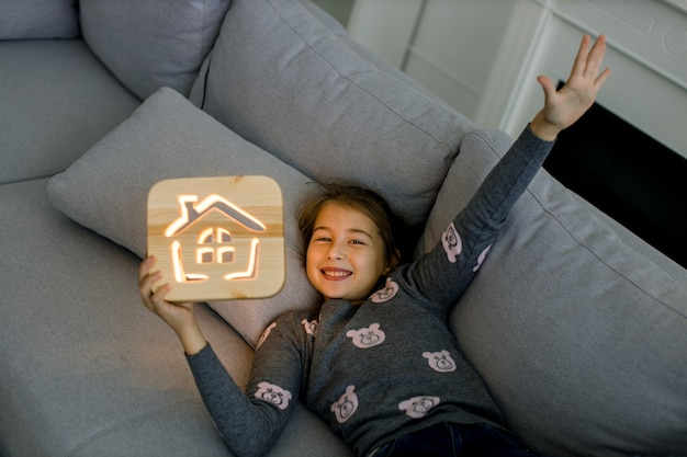 Cozy wooden decorations. night lapms at home. pretty little smiling child girl, lying on gray sofa at home living room interior with wooden night lamp with house picture.