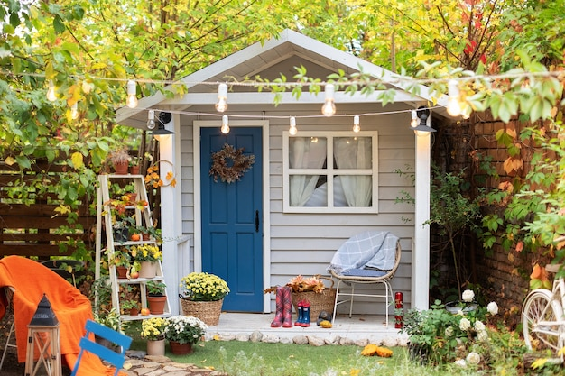의자, 화분에 심은 꽃이있는 아늑한 목조 주택 현관. 가을 마당 장식