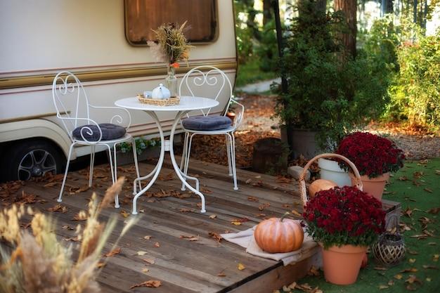 庭の家具が付いている居心地の良い木造の家のポーチ。装飾夏の庭。鉢植えの菊のある居心地の良いインテリアパティオ。庭の居心地の良いレトロなキャラバントレーラーの外に置かれたティーセット付きのテーブルと椅子。
