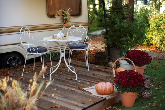 Cozy wooden house porch with garden furniture. decor summer yard. interior cozy patio with chrysanthemums in pots. table and chairs with tea set placed outside cozy retro caravan trailer in garden.