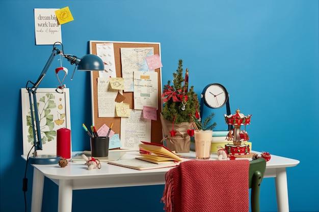 Accogliente spazio di lavoro con albero di natale decorato, bevanda invernale tradizionale, lavagna con foglietti adesivi da ricordare, lampada da scrivania per una buona illuminazione.