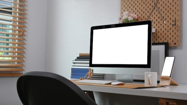 Уютное рабочее место с компьютером, смартфоном и в домашнем или домашнем офисном интерьере.