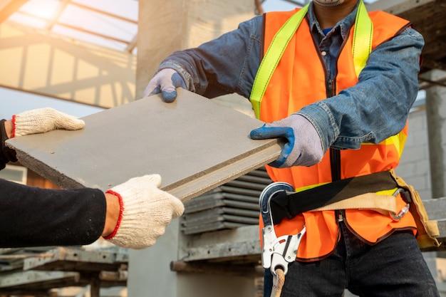 Cpac屋根技術者、住宅建築用cpac屋根瓦、cpacモニエクール屋根システムを設置する建設作業員、タイルの下の断熱反射バリアと軒下の通気孔。