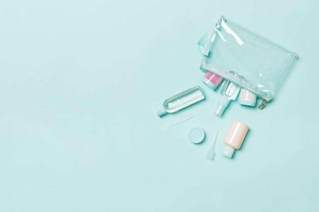 フェイスケアのための手段の平面図:トニックのボトルと瓶、ミセルクレンジング水、クリーム、青の綿パッド。あなたのアイデアのための空のcpaceとボディケア