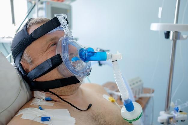 白人男性患者は、集中治療部でcpapマスクを使用してcpap療法を行います。