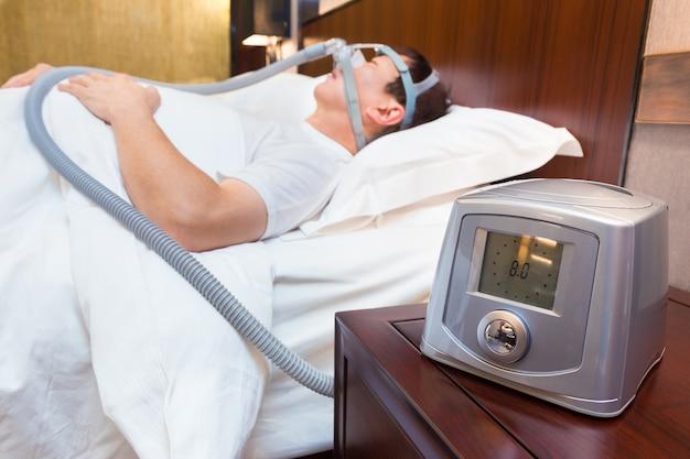 Cpapマスクを身に着けている彼のベッドのアジア人とベッドサイドテーブルに座っているcpapマシン