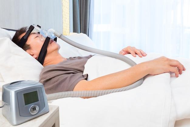 空気中のホースと機械に接続しているcpapマスクを着用中世のアジア人睡眠