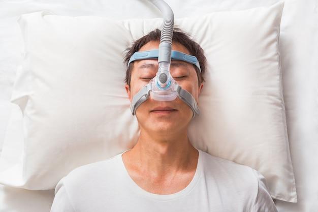 睡眠時無呼吸症候群の人のためのcpapマスクを着用して彼のベッドで眠っている中年のアジア人