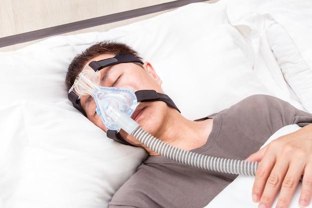 エアーホースに接続されたcpapヘッドギアマスクを着用して彼のベッドで眠っている中年のアジア人