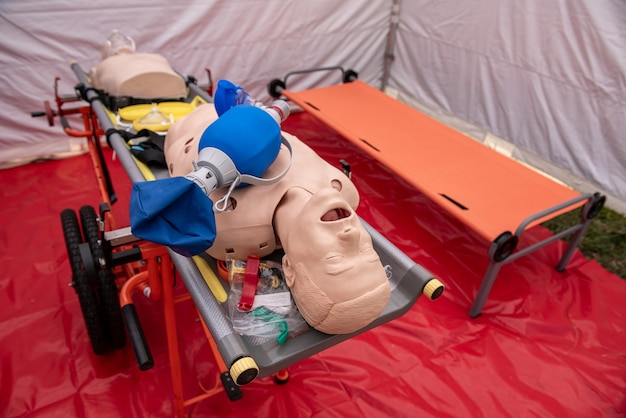 Cpr airway management training medical procedure aed and bag mask valve , demonstrating chest compressions on cpr doll in mobile hospital