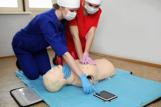 Слр. команда врачей работает над манекеном непрямого массажа сердца и искусственной вентиляции легких. две молодые девушки медсестры занимаются симулятором больничной палаты. скорая помощь фельдшера