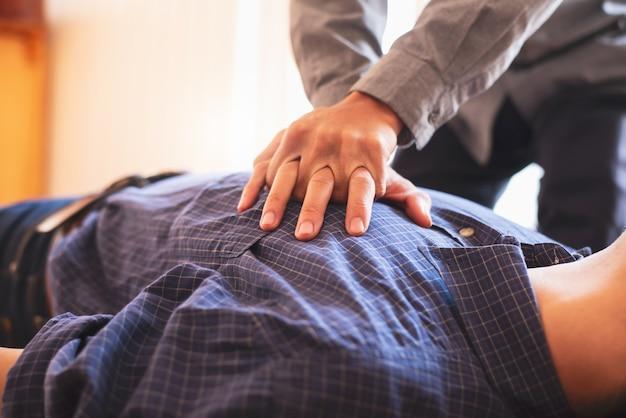 若いビジネスマンは応急処置緊急cprの胸にポンプします。