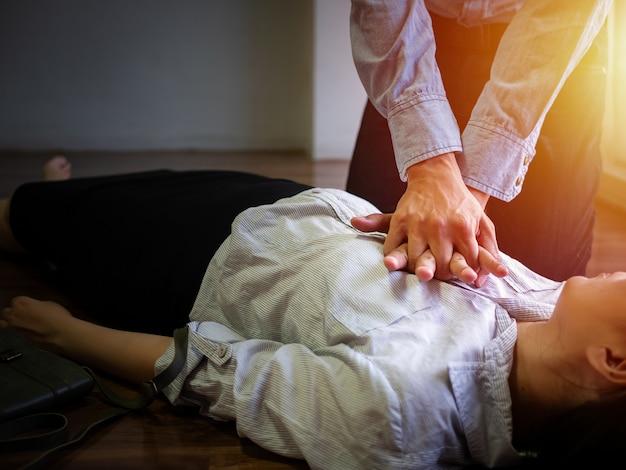 応急処置緊急cprのためのボランティア事務所の男性が胸にハンドポンプを使用