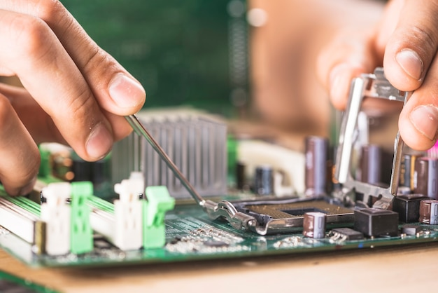 コンピュータのマザーボード上のcpuソケットを修復するit技術者のクローズアップ