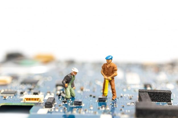 Cpuボードに取り組んでいるミニチュアの人々