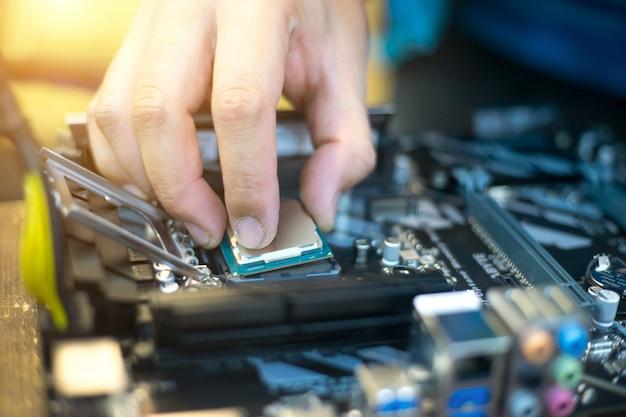 技術者はcpuマイクロプロセッサをマザーボードソケットに差し込んでください。ワークショップの背景