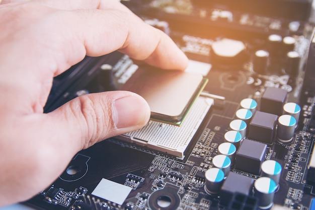 技術者がcpuチップマイクロプロセッサをマザーボード上のソケットに取り付ける