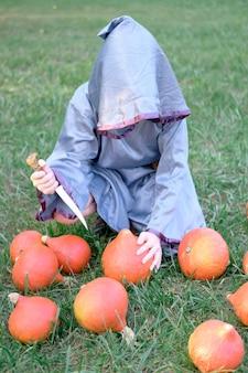 ウィザードの衣装を着た少年は芝生の上に座って、聖cra式にカボチャを切ります。ハロウィーンのコンセプト。