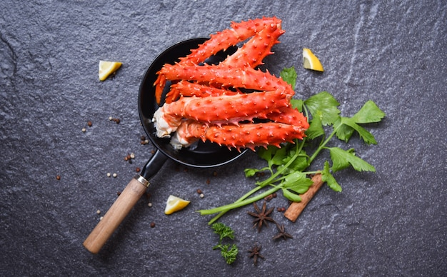 Crab legs in pot on dark background alaskan king crab hokkaido seafood cooked lemon herbs and spices