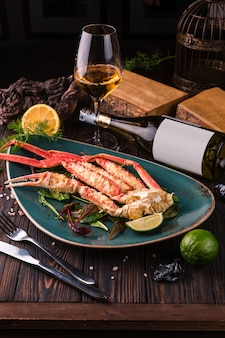 Crab legs with fresh lemon slices in a green plate on a dark wooden table.