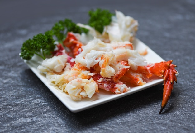 Crab meat on white plate with spices for cooked seafood - red crab legs