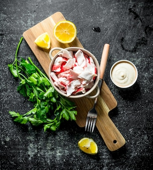 Crab meat with parsley, lemon slices and sauce. on dark rustic background