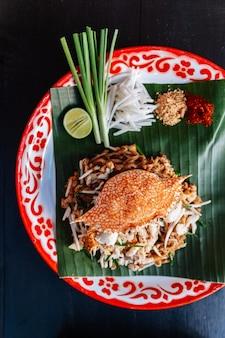 カニ・パッド・タイは、ライム、スカリオン、コショウなどを添えました。粉砕ピーナッツと唐辛子粉。