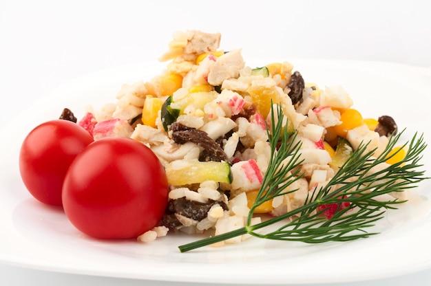 カニのサラダ、トマト2個、ディルの小枝。白い背景に