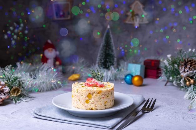 Крабовый салат с кукурузой и яйцами на белой тарелке. новый год и рождество. традиционный русский салат
