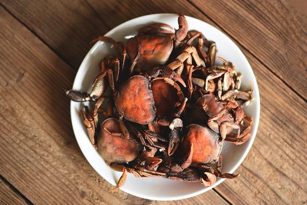 カニの蒸し料理、白いプレートでの新鮮なカニの岩の野生の淡水料理、森のカニまたは石のカニの川
