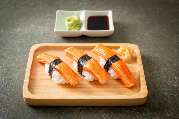Суши с крабовой палочкой на деревянной тарелке - японская кухня
