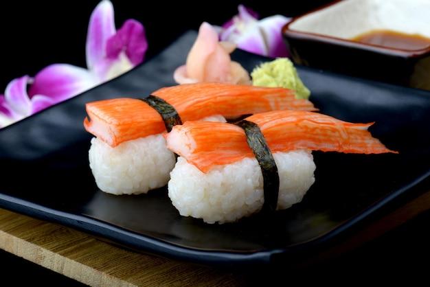Суши с крабовой палочкой или японские суши кани на черной тарелке с васаби и соусом для суши с мигающим освещением.