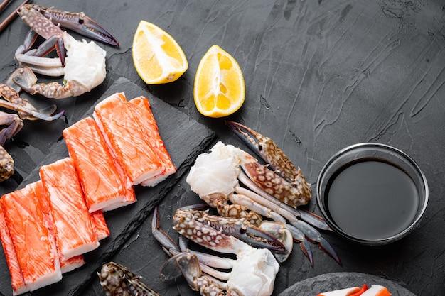 Крабовые палочки, полуфабрикаты из морепродуктов, рыбный фарш с набором синего плавательного краба, на черном фоне, плоская планировка, вид сверху, с copyspace и местом для текста