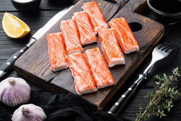 Крабовые палочки из морепродуктов, полуфабрикаты, рыбный фарш с набором синего плавательного краба, на деревянной разделочной доске, на фоне черного деревянного стола