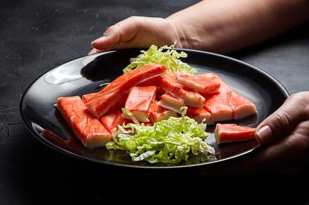 Крабовые палочки со свежей капустой напа. женские руки повара с черной тарелкой. имитация крабового мяса