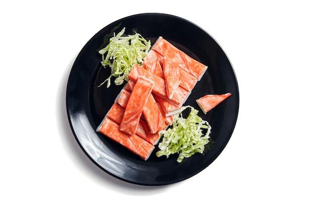 白い背景で隔離の黒いプレートの新鮮な白菜とカニカマ。カニカマの模造品