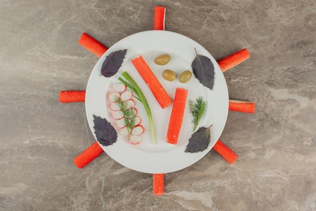 Крабовые палочки с зеленью на белой тарелке.