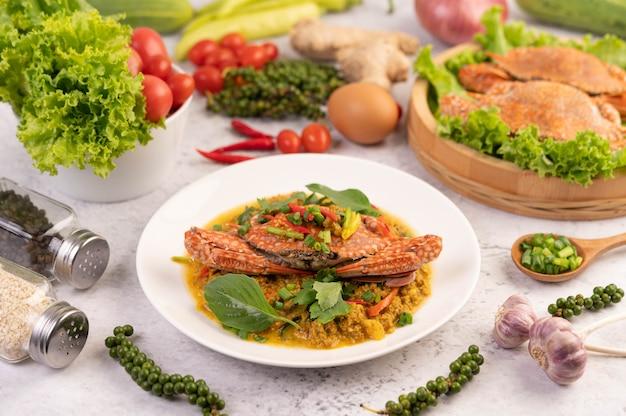 Curry in padella del granchio su un piatto bianco sul pavimento del cemento.