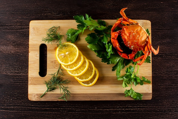 Crab with lemon and parsley on a cutting board