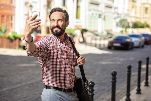 笑顔を割る。通りに立っている間selfiesを作るうれしそうな笑顔の男