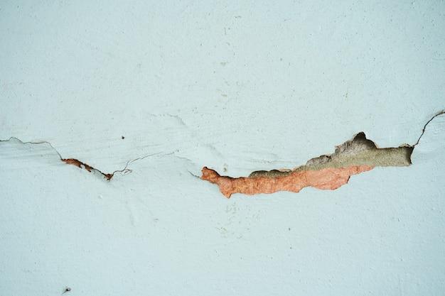 Трещина на окрашенной в синий цвет бетонной стене.