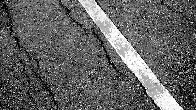 Crack and texture of asphalt road with white dashed line top view background.