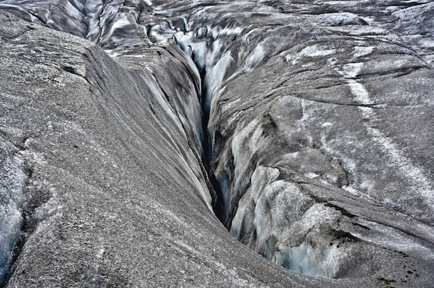 Crack in vatnajökull glacier, located in southern iceland. the mixture of ash and ice gives it its characteristic grey color. on this site the movie interstellar was filmed