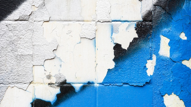 Crack of white and blue paint at the wall