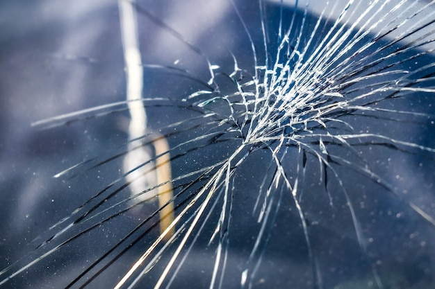 Crack on windshield of car. white cracks in glass. automotive glass requiring repair or replacement.